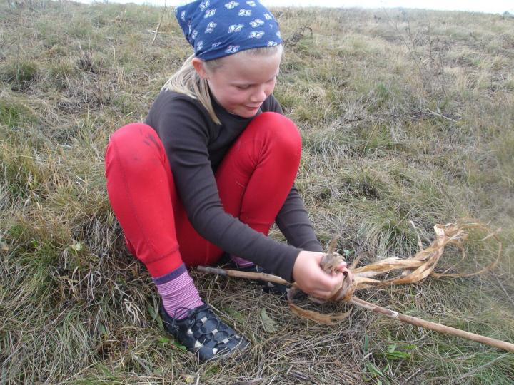 Agnes leger med en pind, hun har fundet på campingpladsen. Legetøjet ligger derhjemme i Danmark