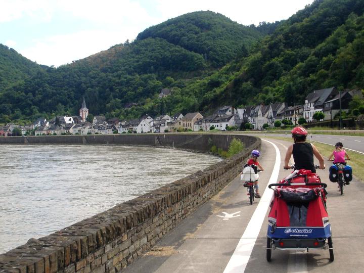 Familien Møller cykler på cykelsti langs Rhinen